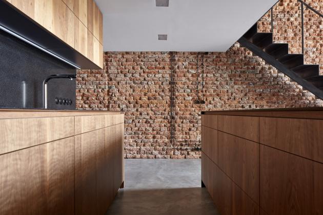 Dokonale zpracované schodiště se surově řešenou zdí zcihel přesně konvenuje se záměrem architektů, ato uchovat industriálního ducha vtěchto nestandardních prostorách