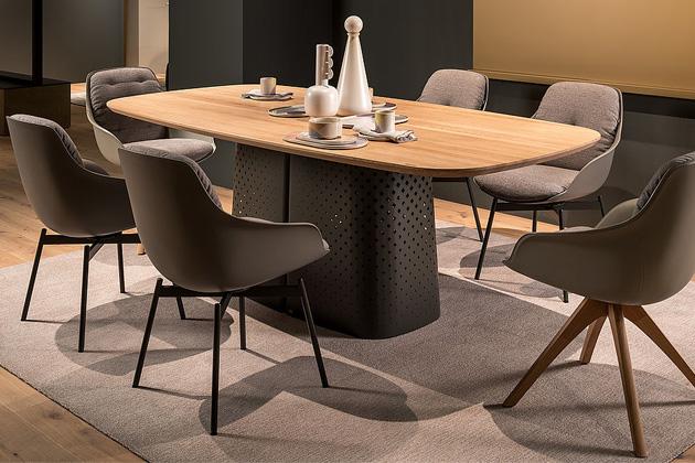 Jídelní stůl Rolf Benz 929 je složen zorganicky tvarované desky zpřírodního kamene nebo masivního dřeva a ocelové základny shladkou povrchovou úpravou sperforovaným vzorem.