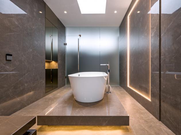 """Hlavní koupelně vévodí solitérní vana, pro kterou autoři nechali vytvořit """"pódium"""", aby vprostoru vynikla aaby zdůraznili krásu prostor svysokým stropem. Při užívání vany se majitelé mohou kochat pohledem střešním oknem do nebe"""