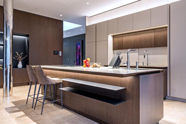 Kuchyň je vyrobena zjednoho kusu velkoformátové keramiky. Kromě moderní výsuvné digestoře se architekti rozhodli všechny spotřebiče amalé elektrické pomocníky skrýt za dvířky kuchyňského nábytku, aby nenarušovaly komplexní zážitek zpolyfunkčního prostoru. Kromě dvou dřezů vkuchyňské zóně architekti použili mnoho dalších praktických vychytávek jako například uzavíratelnou niku za dřezem vkuchyňské nábytkové části ustěny