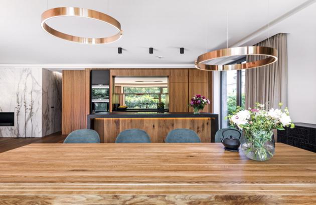 Architekt kuchyň jakoby utajil do uzavíratelného skříňového systému, ze kterého vystupuje skvostně podsvícené mosazné zrcadlo, které je položeno na zeď za kamennou pracovní deskou. Druhou část kuchyně tvoří kuchyňský ostrůvek ze žuly