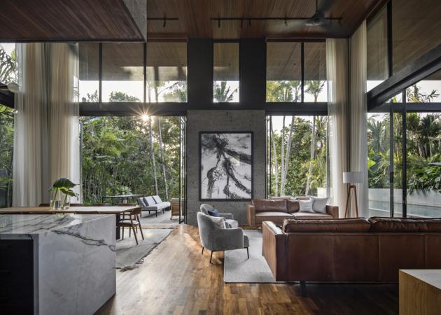 Sofa potažená hnědou kůží i výrazné tvarosloví křesílek ve společné části domu odkazují na elegantní styl 50. let