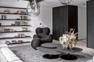 Obývacímu pokoji vévodí křivky ikonického křesla Up Gaetana Pesceho a sedací soupravy Tufty Time Patricie Urquioly (BB Italia). Efektní obraz dotvářejí stropní svítidla Tim (Bomma) designérů studia Olgoj Chorchoj