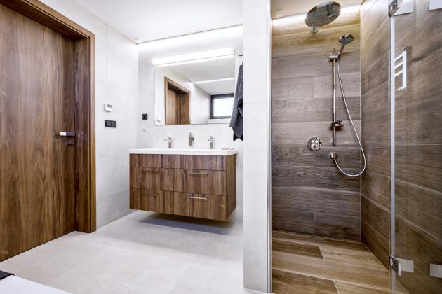 Koupelna v patře zahrnuje dvojité umyvadlo a kromě sprchování umožňuje i koupel ve vaně