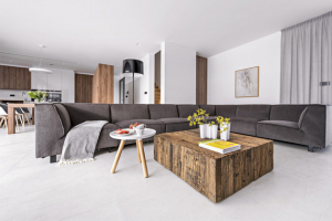 Odpočívat lze na čalouněné rohové sedací soupravě (Furninova) v šedém odstínu, kterou doplňuje konferenční stolek v imitaci rustikálního masivu dřeva (Symerský) a stojací lampa (Flos)