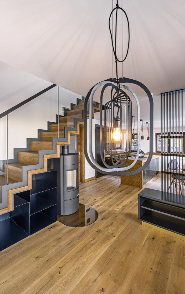 Materiálem prostupujícím celý interiér je antracitový plech, který se objevuje na řadě dominantních prvků od lamel opticky rozdělujících prostor přes svítidla až po krb a dřevník