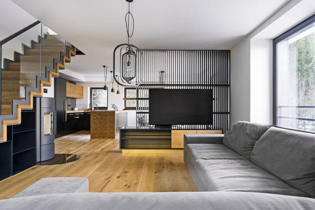 Dostatek přirozeného denního světla a množství použitého dřeva umožnilo vytvořit ryze pánský interiér plný kovu, industriálních detailů a antracitových odstínů, který přitom působí elegantně a vzdušně zároveň