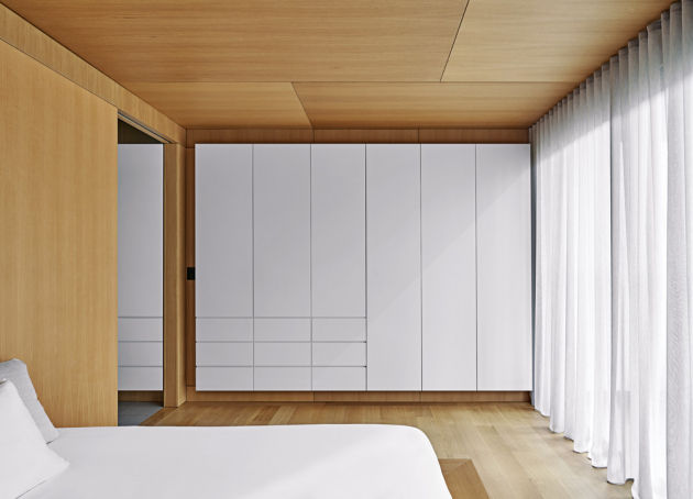 Snížený strop, dřevěné obložení a textilní závěsy, které v rámci tohoto interiéru nikde jinde nenajdete, tvoří z ložnice útulnou oázu uprostřed velkorysého loftu