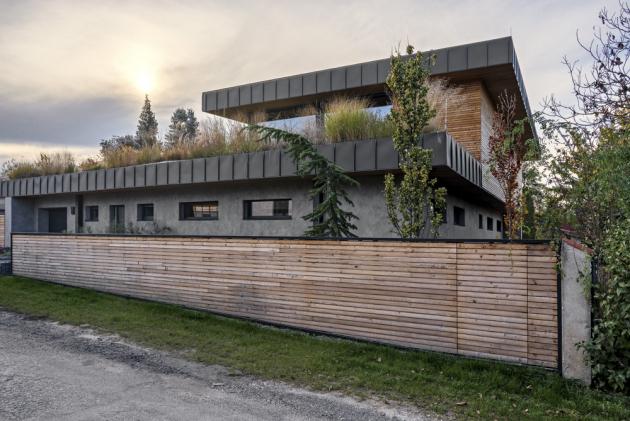 Koncepce domu byla navržena bez plotu, autor si vysnil projekt otevřený okolí, vyšperkovaný lavičkou z vlastní dílny, která by byla posazena předdůmdoulice. Nakonec se investor rozhodl i přes apel autora plot dostavět. To je ze strany architekta vnímáno jako jistý handicap