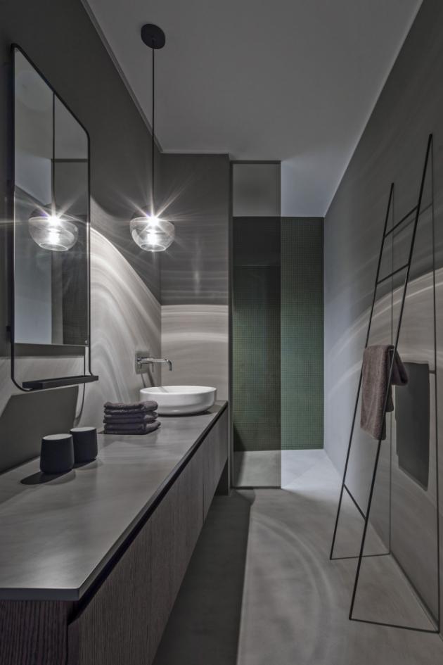 Koupelnu vpříjemných tlumených barvách, ošetřenou stěrkou, oživuje zelený obklad walk-in sprchového koutu skouřově zabarveným sklem. Nábytek je zhotovený na míru ztmavě tónované dubové dýhy. Miskové keramické umyvadlo (Kolo Ego, Antonio Citterio) doplňuje nástěnná baterie (Gessi)