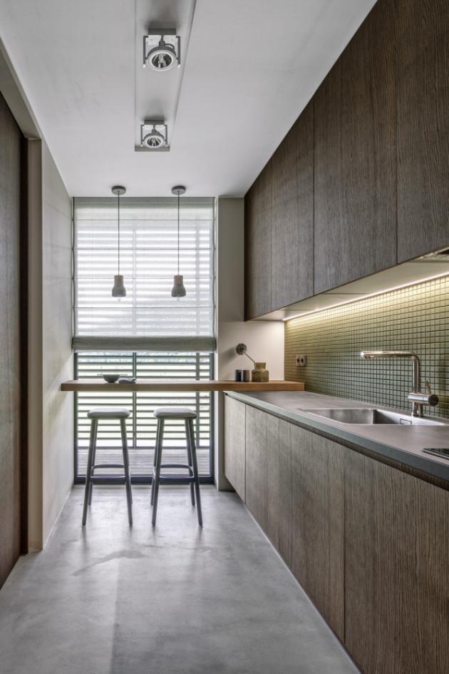 Do malé kuchyňky se vešel jen malý, na míru vyrobený stůl sbarovými židlemi (Pedrali). Nábytek kuchyňské linky ztmavě mořené dubové dýhy doprovází obklad ze zelené mozaiky. Dřez abaterie nesou značku Blanco