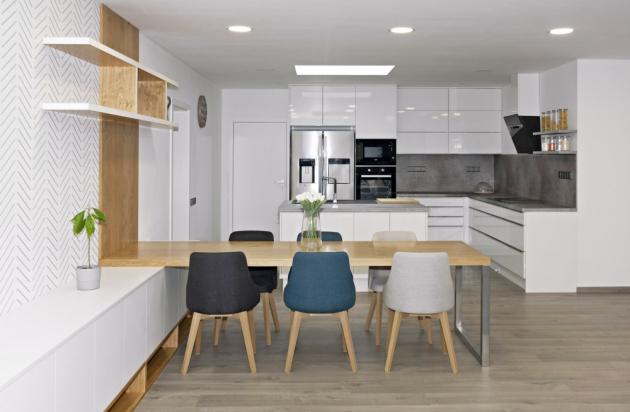 Jídelní stůl navazuje na úložný systém obývacího pokoje. Součástí multifunkčního prostoru je také kuchyně v provedení vysoký lesk s praktickým ostrůvkem