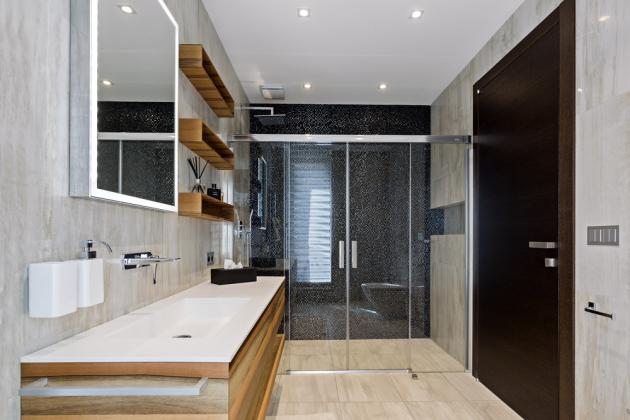 Nábytek v koupelně pro hosty (Ideagroup, série Cubik) má povrch z ořechové dýhy, na podlaze a na stěnách je dlažba s dekorem mramoru, ve sprchovém koutě je jedna stěna obložená plastickou mozaikou