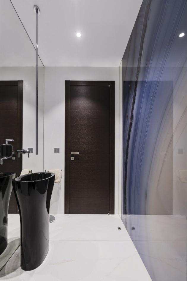 Výrazným prvkem místnosti s toaletou je černé podlahové umyvadlo se stropní baterií a obklad s dekorem onyxu, který se odráží v zrcadlové stěně u umyvadla