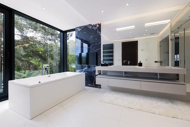V hlavní koupelně je velký nábytkový prvek s integrovanými umyvadly a povrchem z materiálu Ecomalta (Ideagroup, série Cubik) a sprchový kout. Výrazným prvkem je obklad s výraznou kresbou onyxu (Ava Ceramica)