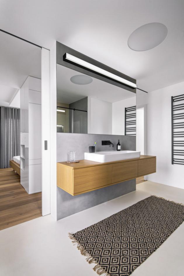 V koupelně jsou použity černé koncové prvky, na podlaze je cementová stěrka, na stěnách ve sprchovém koutě pak šestiúhelníkový obklad. Ručně tkaný jutový koberec je z Nila store