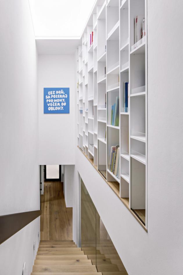Knihovna prorůstá podél schodiště z přízemí do prvního patra
