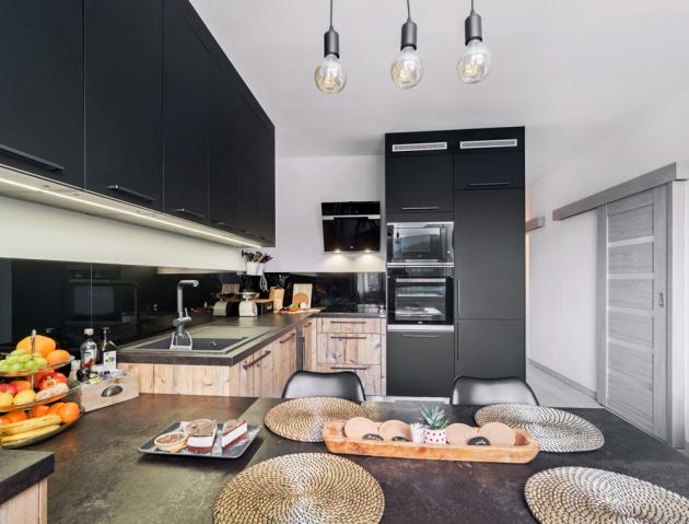 V přední části kuchyně vymezené jídelním stolem je přípravná část. Varná a mycí zóna jsou oddělené prostornou pracovní plochou, jejíž hloubka se díky instalačním potřebám o několik centimetrů rozšířila