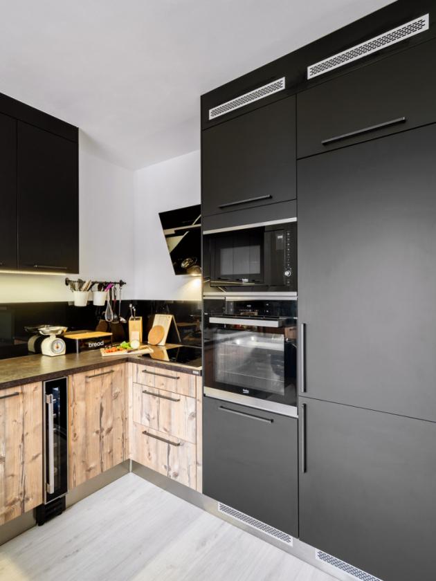 V místě, kde byla původní kuchyňská linka, je varná deska s digestoří, vysoký nábytkový modul se zabudovanými spotřebiči a dalšími úložnými prostory. Spodní rohová skříňka je vybavena výsuvným systémem