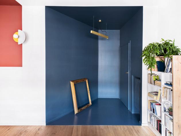 Vstupní prostor bytu tvoří sytě modrá výmalba. Akcentem je zde odstín zlaté, opakující se na klice, závěsném svítidle i na dekorativním rámu
