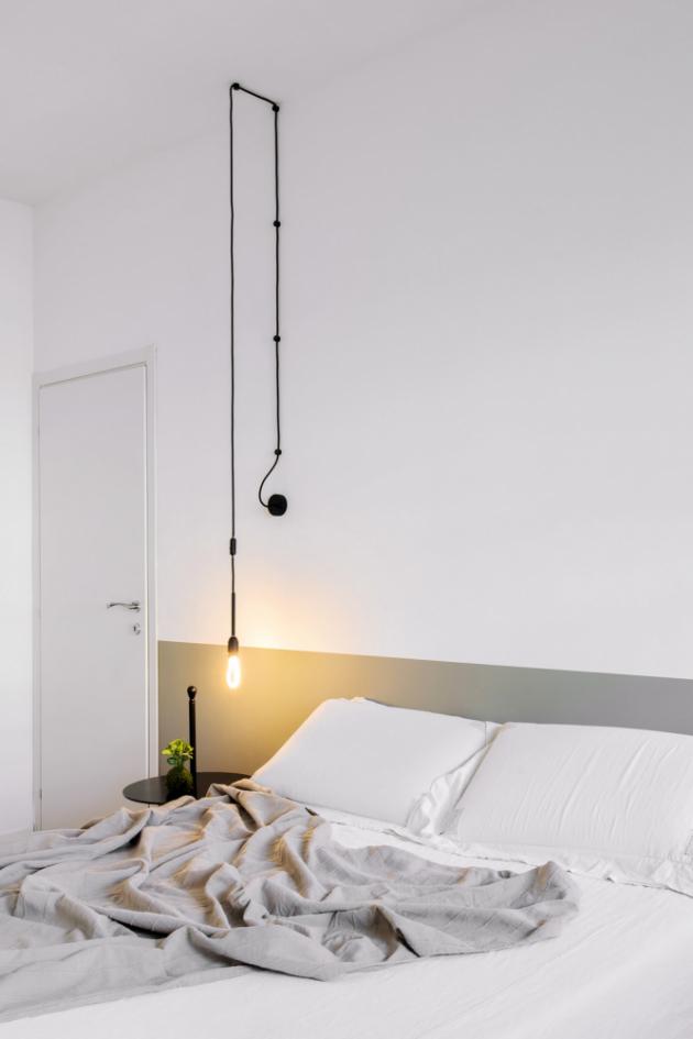 Nejvýraznějším prvkem jednoduché ložnice je svítidlo vedené po stěně a přes strop, nahrazující klasickou stolní lampu