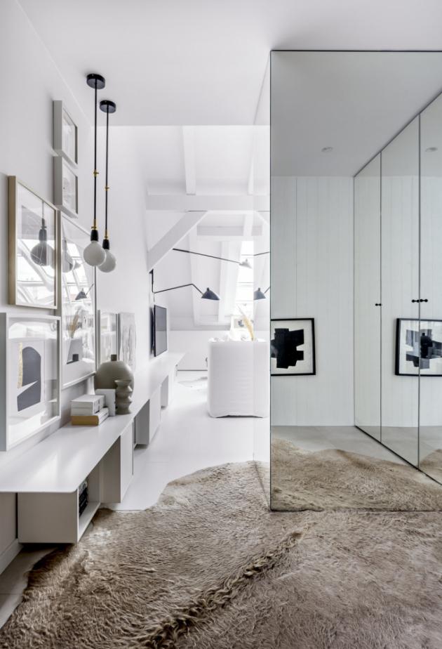 Úložné prostory ve vstupní chodbě jsou opatřeny dveřmi se zrcadly. Bíle lakované police z kovu v celkové délce sedmi metrů jsou vyrobené na míru a doplněné typovými nábytkovými skříňkami různých hloubek (IKEA)