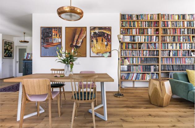Dominantou obývacího pokoje je knihovna vyrobená z 350 kilogramů dřeva. Zelenou pohovku (Mesonica Puzo) z Bonami doplňují stolky – konferenční a přístavný stolek z pařezu (Nafurt), který dostal Lukáš darem ke 40. narozeninám