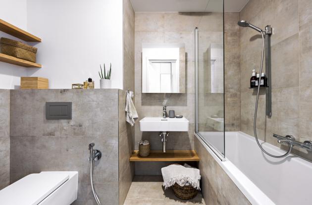 Dispoziční rozvržení původní koupelny zůstalo zachováno, ovšem dlažbou (Refinplant 45 x 90 a 60 x 60 cm) obložené stěny i podlaha jsou nové. Umyvadlo a klozet nesou značku Laufen, baterie Hansgrohe a akrylátová vana (Polysan) je doplněná zástěnou Hüppe