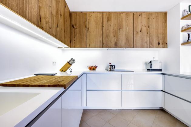Kuchyň situovaná do tvaru písmene U poskytuje velkorysou pracovní plochu. Kapacitu úložných prostor významně rozšiřují horní skříňky vedoucí až ke stropu