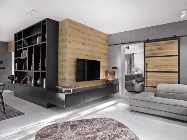 Nábytková stěna z jídelny pokračuje dál přes roh v podobě nízkých skříněk pod zavěšeným televizorem