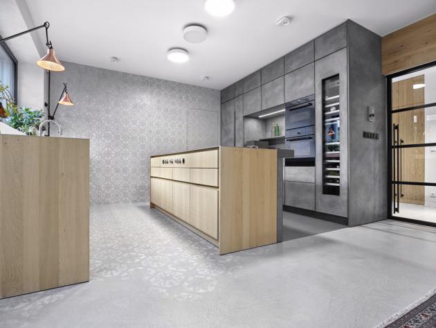 Vysoká sestava kuchyňských skříněk je opatřena šedou betonovou stěrkou. Obsahuje vestavné spotřebiče a vinotéku. Navazující stěna ukrývá dveře se skrytou zárubní od firmy Dorsis, vedoucí do spíže, které se stávají díky stěrce Betonepox Soft (Němec) se vzorem téměř neviditelnými. Kuchyňský ostrůvek je pak navržen z přírodní katrované dýhy v dekoru dubu. Ve varné desce má integrovaný odsavač par, přičemž ovládání je umístěno na přední části ostrůvku. Tento detail vyniká díky bezúchytovému systému