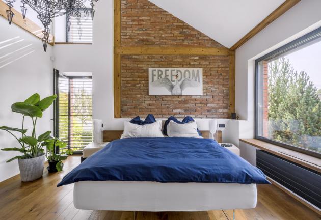 Majitelé domu milují otevřený prostor a netradiční řešení. Kombinace odkrytých cihel, přiznaných trámů, rozměrných oken a vysokých stropů připomíná loftové bydlení a vyloženě ladí s tématem obrazu nad zdánlivě levitující postelí
