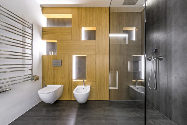Nad toaletou a bidetem je nábytková stěna s uzavřenými skříňka a otevřenými nikami. Nábytek a zástěnu sprchového koutu vyrobili truhláři a sklenáři, se kterými studio Perfecto Design dlouhodobě spolupracuje