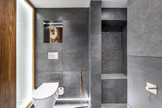 Kromě okna nad zrcadlem přichází do koupelny světlo z přilehlé chodby prosklenou stěnou. Orientační osvětlení zajišťují světelné LED pásky