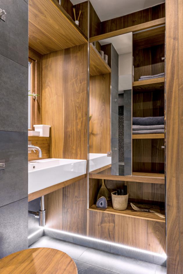 Stěna niky ve sprchovém koutě je obložena mozaikou v šedých odstínech s metalickými prvky. Vedle umyvadla je velký úložný prostor