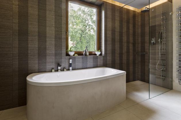 Na sprchový kout typu walk-in se sprchovým žlabem navazuje vana Armonya (Teuco). Na opláštění vany je použita stejná dekorativní stěrka jako na některých stěnách