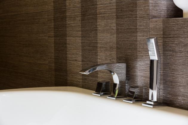 U vany a umyvadla jsou baterie ze série Glitter (Ritmonio). Čtyřotvorová vanová baterie s výsuvnou ruční sprchou je zapuštěná do lemu vany