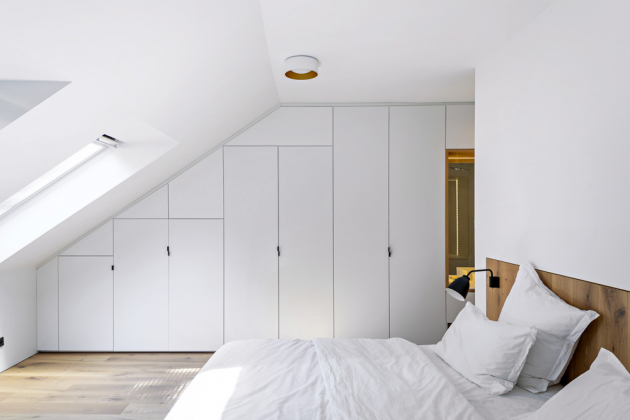 Kombinace dubové dýhy a bílé lakované MDF desky se objevuje v celém bytě včetně ložnice. Lůžko doplňují nástěnné lampičky Caravaggio (Fritz Hansen)
