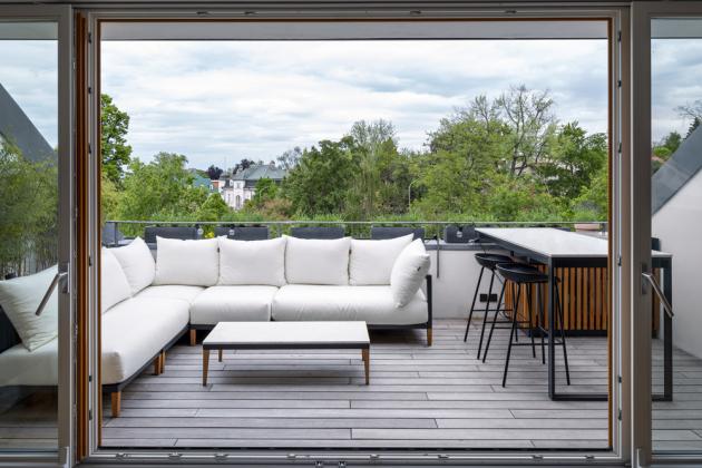 Z obývacího pokoje lze vstoupit přímo na terasu s výhledem na vilu Bianca architekta Jana Kotěry. Terasa je vybavená pohodlným sezením i venkovní kuchyní s grilovacím stolem zhotoveným na míru
