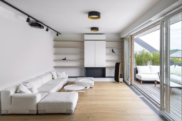 V nábytku nad krbem je rafinovaně ukrytý bar i klimatizace a mezi závěsy, před francouzským oknem, je zabudované projekční plátno