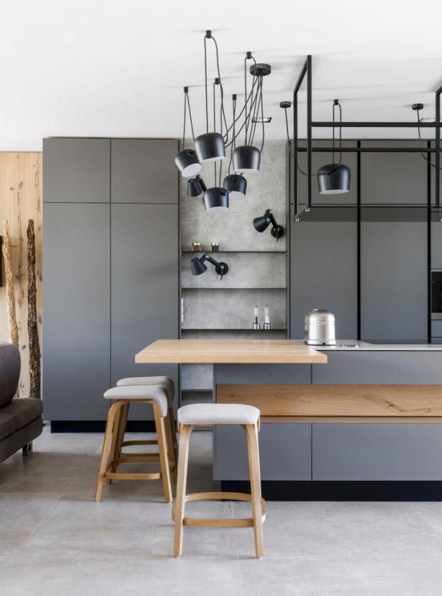 Výrazným estetickým prvkem jsou tmavé kovové prvky a kontury, které člení plochy nábytku. Na konci ostrůvku je širší dubová deska, která slouží jako alternativa jídelního stolu