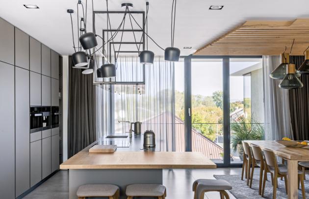 Nevšedním prvkem kuchyně je konstrukce umístěná nad ostrůvkem. Na jejím spodním rámu je kouřové sklo, které vytváří transparentní polici