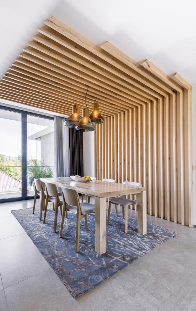 Aby návrhář v interiéru vyvážil opakující se odstíny šedé, začlenil do materiálové skladby přírodní dub v podobě obkladů, jídelního stolu, židlí a nik