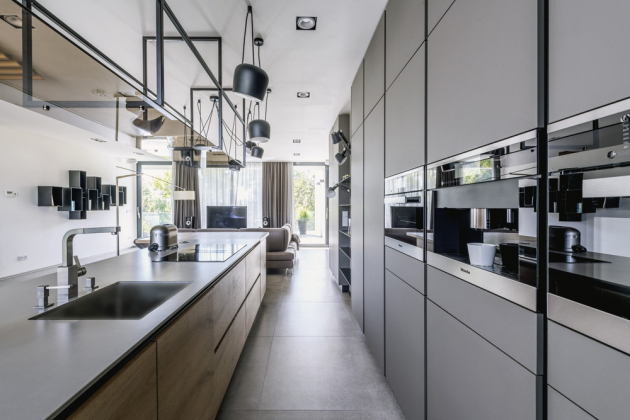 Z jedné stany kuchyňské části je vysoký nábytkový modul s úložnými prostory a vestavnými spotřebiči. Na ostrůvku je varná deska, dřez a prostorná pracovní plocha