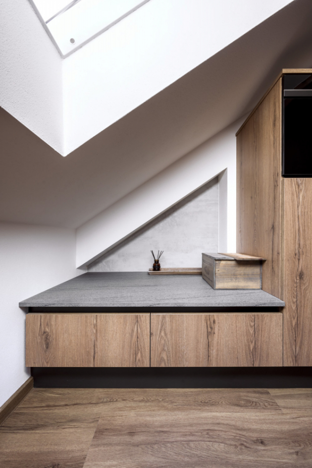 Volný hůře dostupný prostor pod šikminou využila návrhářka k umístění nízkých skříněk a volnou plochou, která může posloužit k umístění dekoračních předmětů