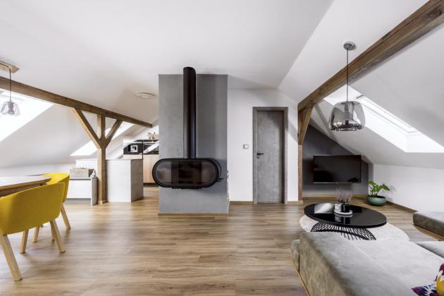 Z pohledu od obývacích prostor je pracovní část kuchyně ukryta příčkou, na které jsou umístěna moderní krbová kamna