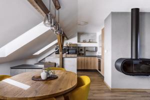 Ke kuchyňské sestavě s dekorem dřeva majitelé pořídili masivní dubový stůl ve stejném odstínu a oživili jej žlutými křesílky