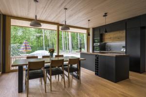 Výrazným materiálem, který se promítá do celého objektu, je dřevo. Příjemným prvkem kuchyňské části jsou portálové prosklené dveře, díky kterým je v místnosti dostatek denního světla. Černá matná dvířka kuchyně působí luxusním dojmem