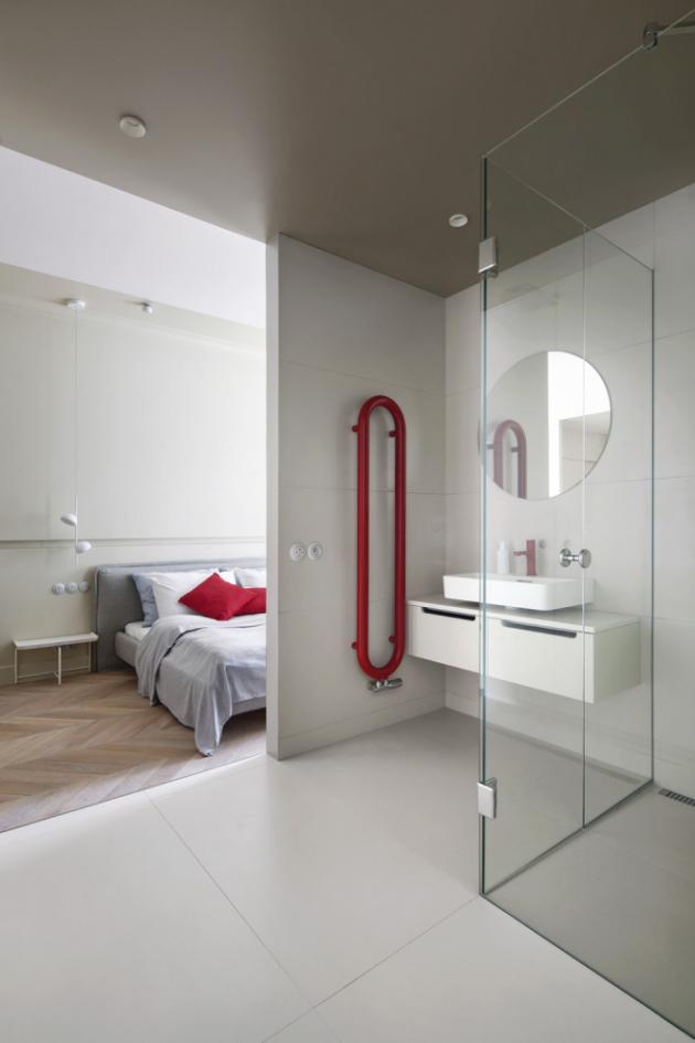Světlý velkoformátový obklad Todatech (Todagres) na stěnách i na podlaze opticky zvětšuje prostor koupelny, vzhledovou dominantou je otopné těleso Coron (Isan) v červené barvě