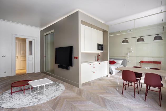 Plochu stolu osvětluje závěsné svítidlo Ambit Rail (Muuto) v odstínu taupe, červené židle jsou z řady Form (Normann Copenhagen). V celém bytě jsou použity zásuvky a vypínače ROO-X (Katy Paty) v hravém retro stylu